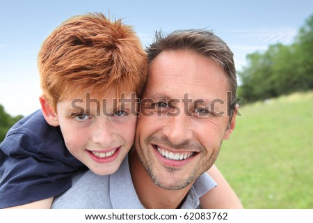 Closeup of father and son in countryside - stock photo