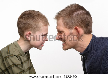 closeup of father and son with angry faces close together - stock photo