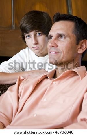 Closeup of father with teenage son at home on sofa - stock photo