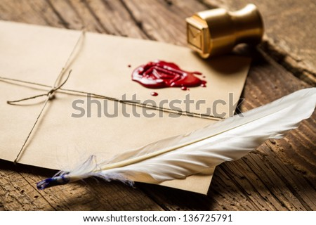 Closeup of feather on envelope with red sealant and metal stamp - stock photo