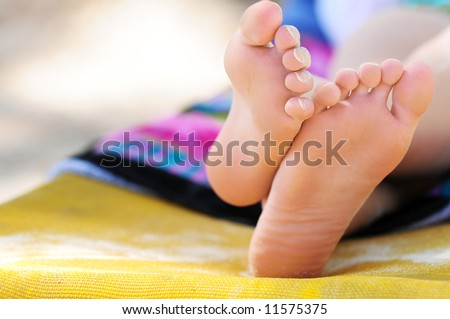 Closeup of feet of a young girl in chaise lounge relaxing on a beach