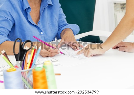 Closeup of female designers  having a meeting in a fashion design studio. A sketch was made of me. - stock photo
