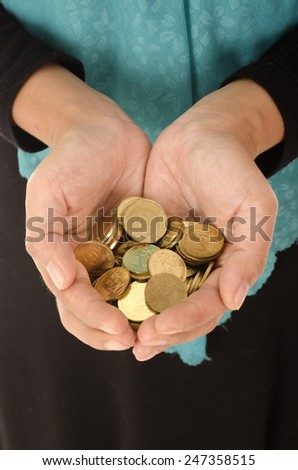 Closeup of female hand holding coins, saving concept - stock photo