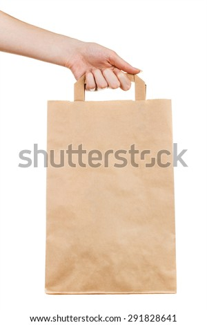 Closeup of female hand holding kraft paper bag isolated on white background - stock photo