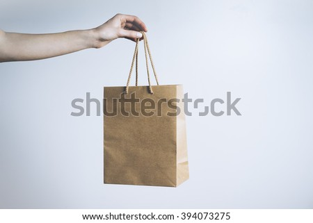 Closeup of female hand holding mock up of craft paper package - stock photo