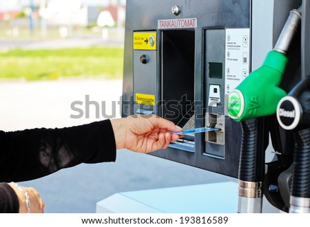 Closeup of female hand   inserting a credit card into an automated gas pump. - stock photo
