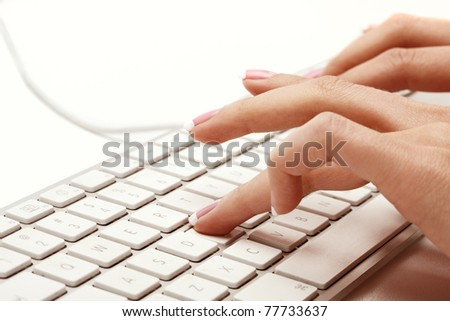 Closeup of female hand with manicure typing on white keyboard