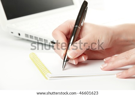 Closeup of female hand writing notes on the notepad. - stock photo