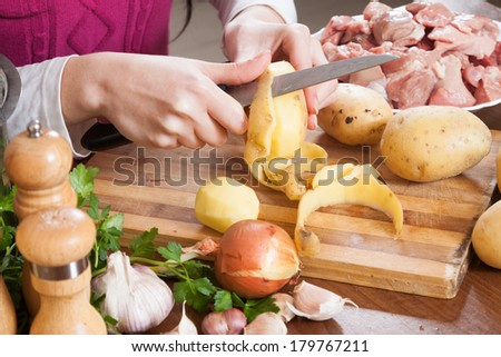 Closeup of female hands cleaning potatoes at table in  kitchen