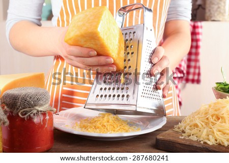 Closeup of female hands grating cheese - stock photo