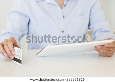 Closeup of female hands holding a credit card and shopping online with digital tablet. - stock photo