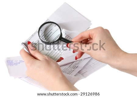 Closeup of female hands holding a magnifying glass on the bills. Isolated on white background.