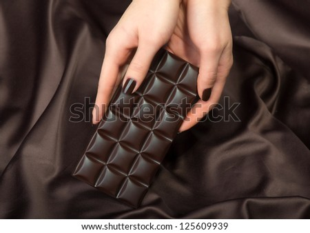 Closeup of female hands holding the dark chocolate bar