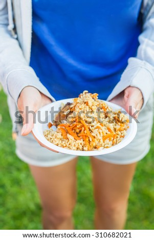 Closeup of female hands holding white plastic plate of pilaf outdoors. Shallow DOF - stock photo