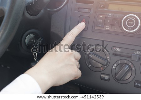Closeup of female hands pushing emergency button in car