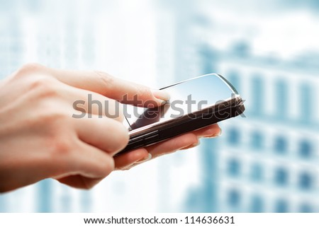 Closeup of female hands using a smart phone. City background.