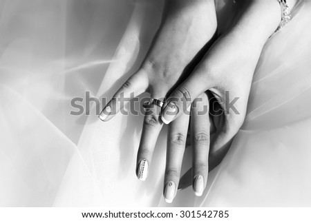 Closeup of female hands with beautiful wedding ring from precious metal on viel fabric of bride dress black and white, horizontal picture - stock photo