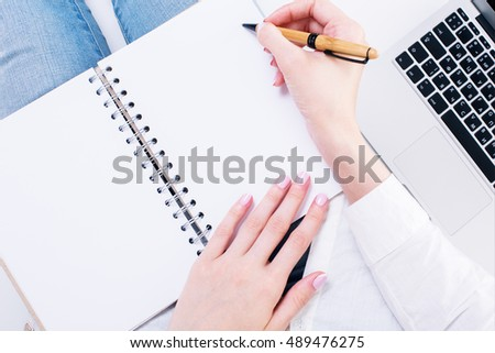 Closeup of female hands writing in blank spiral notepad placed on her lap next to laptop keyboard. Mock up