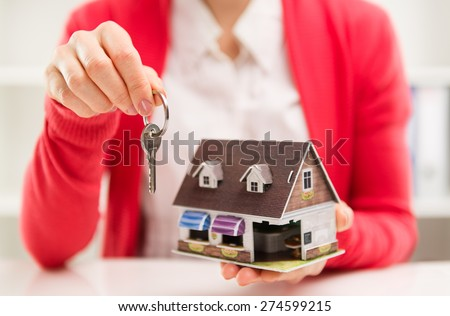 Closeup of female house agent holding keyring of rented house. Real estate contract. Shallow depth of field. - stock photo