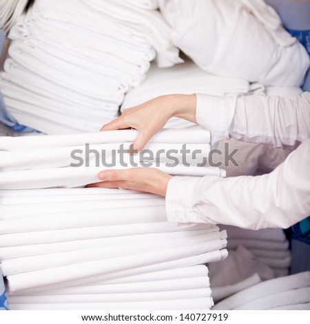Closeup of female housekeeper's hands stacking sheet in stock room - stock photo