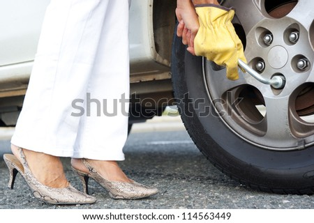 Closeup of female legs in high heel shoes and hands with gloves plus tool to change tyre at car.