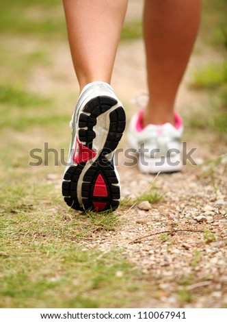 Closeup of female legs jogging on a trail - stock photo