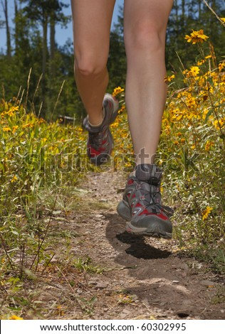 Closeup of female legs jogging on a trail.