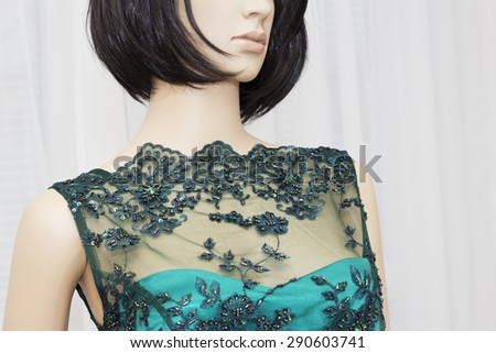 Closeup of female mannequin wearing a beautiful green dress of lace pattern with  crystals .  - stock photo