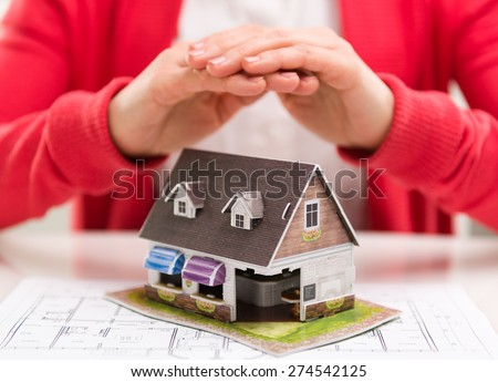 Closeup of female realtor hands showing new house model to client. Concept of real estate purchase and insurance. Shallow depth of field.