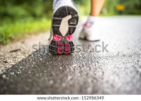 Closeup of female running on a wet road. - stock photo