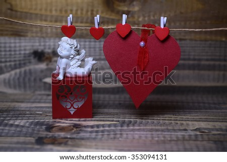 Closeup of few beautiful cupid angel decorative figurine near red paper greeting valentine box and card on hanging ribbon on clothes-peg with no people on wooden background copy space, horizontal - stock photo