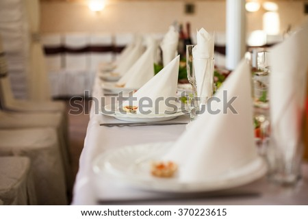 Closeup of fine dinning tableware and silverware catered at wedding reception - stock photo