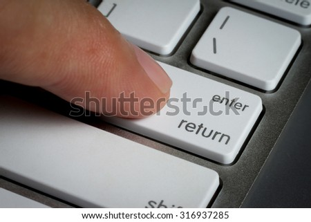 Closeup of finger on enter key in a keyboard. - stock photo