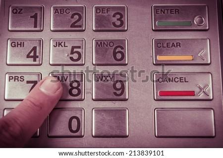 Closeup of finger pressing atm machine metallic keyboard - stock photo