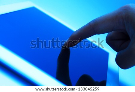 closeup of finger touching screen on tablet-pc with shallow depth of field blue toned - stock photo