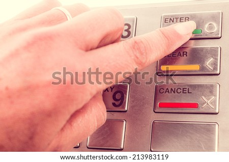 Closeup of finger using atm machine with metallic keyboard - stock photo