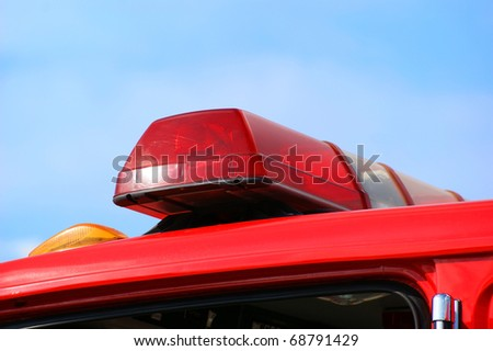 Closeup of fire truck top lights against blue sky background. - stock photo