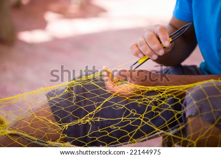 Closeup of fisherman repairing fishing net - stock photo