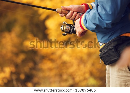 Closeup of Fisherman`s hand with spinning - autumn fishing season. - stock photo