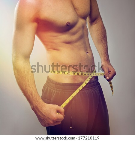 Closeup of fit young Caucasian man's torso. Man using tape measure. Fitness, diet, healthy lifestyle. - stock photo