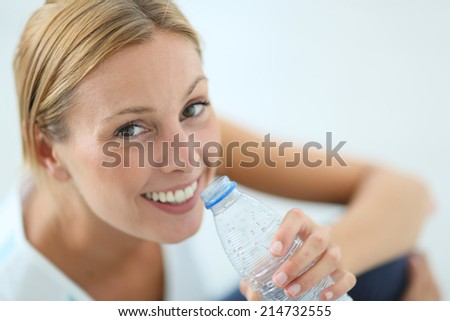 Closeup of fitness girl drinking water after exercising - stock photo