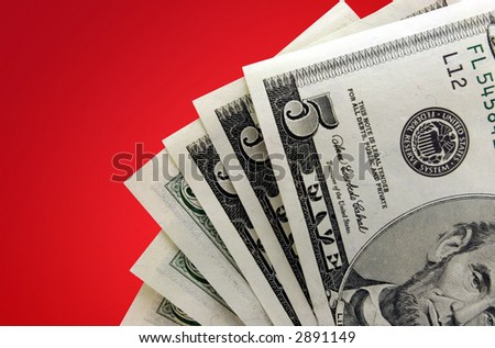 Closeup of five dollar bills against red gradient background. - stock photo