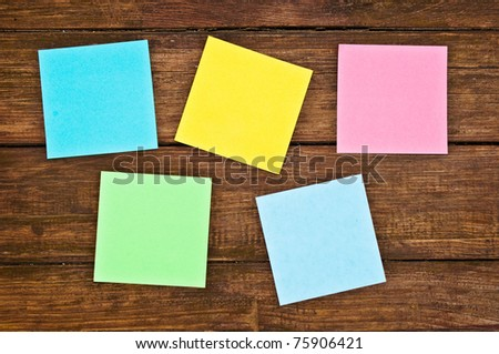 closeup of five empty multicolor reminder notes on the wooden background