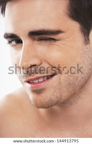 Closeup of flirtatious young man winking on white background - stock photo