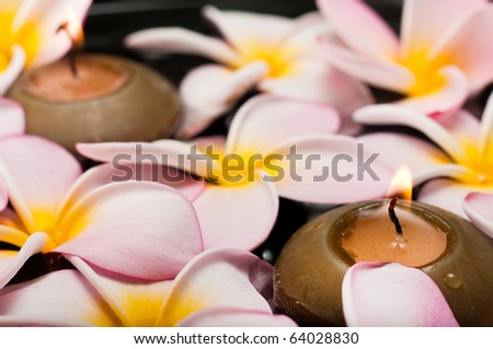 Closeup of floating frangipani flowers and candles - stock photo