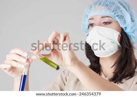 Closeup of Focused Caucasian Female Scientist Making Solution into the Glass Flask. Over Gray Background. Focus on Eyes. Horizontal Image - stock photo