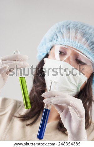 Closeup of Focused Caucasian Female Scientist Making Solution into the Glass Flask. Over Gray Background. Vertical Image - stock photo