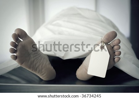 Closeup of foot in a morgue with blank tag hanging from the big toe. - stock photo