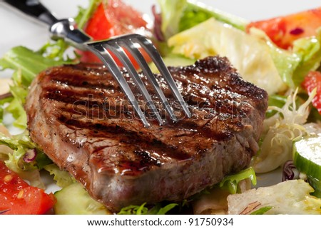 closeup of fork on a grilled steak
