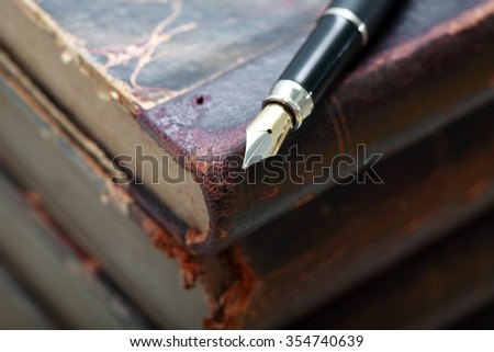 Closeup of fountain pen on stack of old books - stock photo